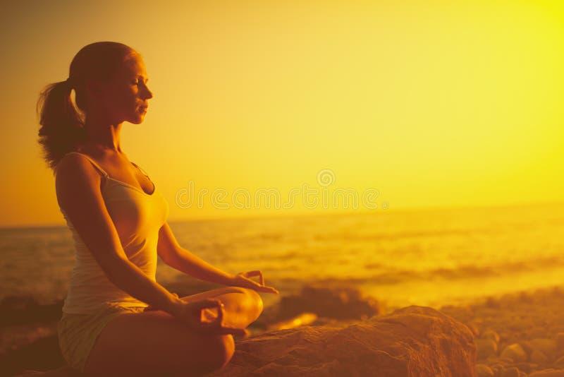 Женщина размышляя в представлении лотоса на пляж на заходе солнца стоковые фотографии rf