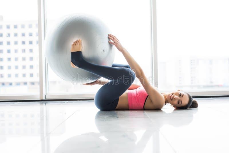 Женщина разрабатывая с шариком тренировки в спортзале Женщина Pilates делая тренировки в комнате разминки спортзала с шариком фит стоковое изображение