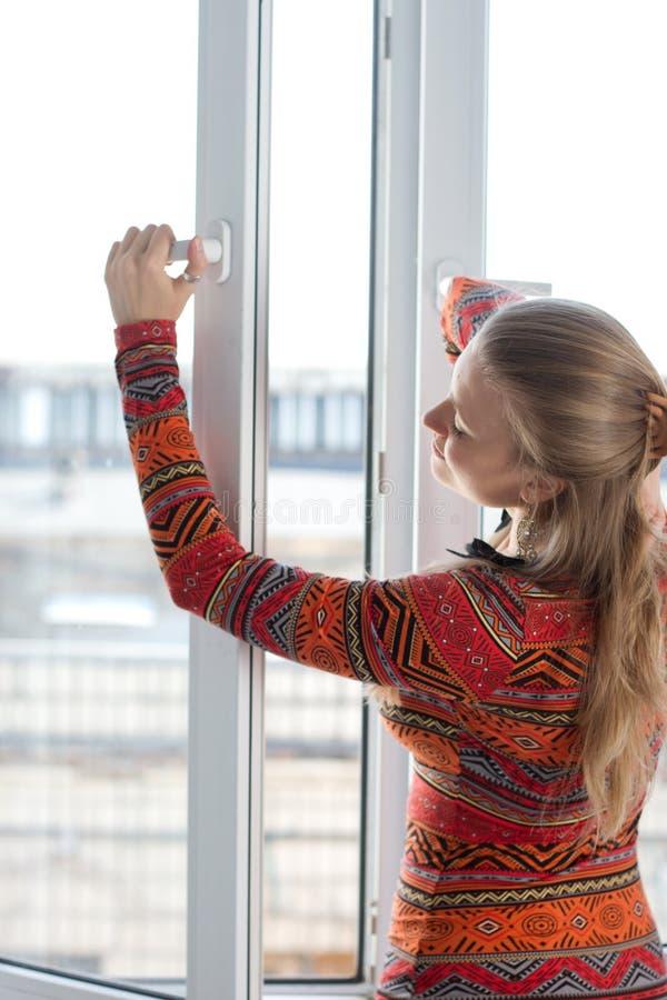 Женщина раскрывает пластичное окно стоковое изображение rf