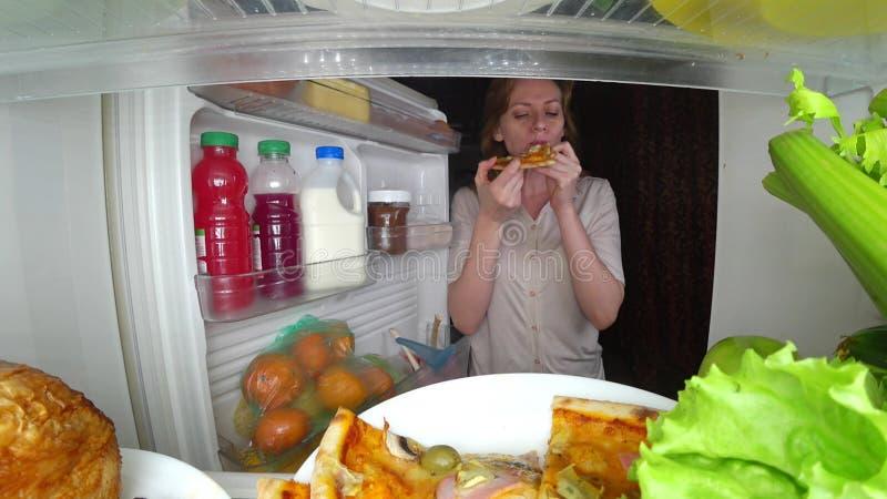 Женщина раскрывает холодильник на ноче Голод ночи обжорство диеты стоковое фото rf
