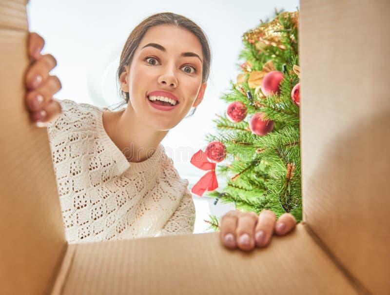 Женщина раскрывая подарок на рождество стоковая фотография