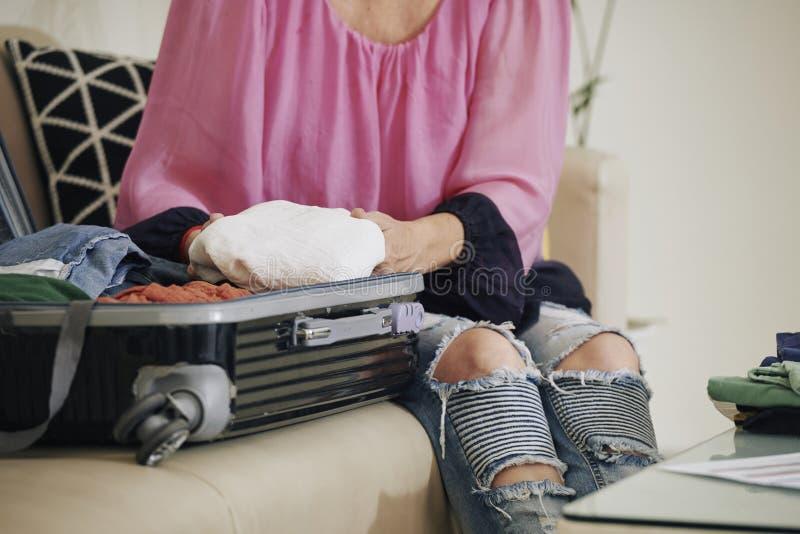 Женщина распаковывая чемодан стоковое изображение