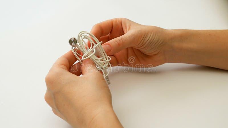 Женщина распутывает запутанные earbuds или узел наушника стоковое изображение rf