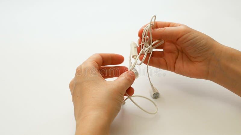 Женщина распутывает запутанные earbuds или узел наушника стоковая фотография