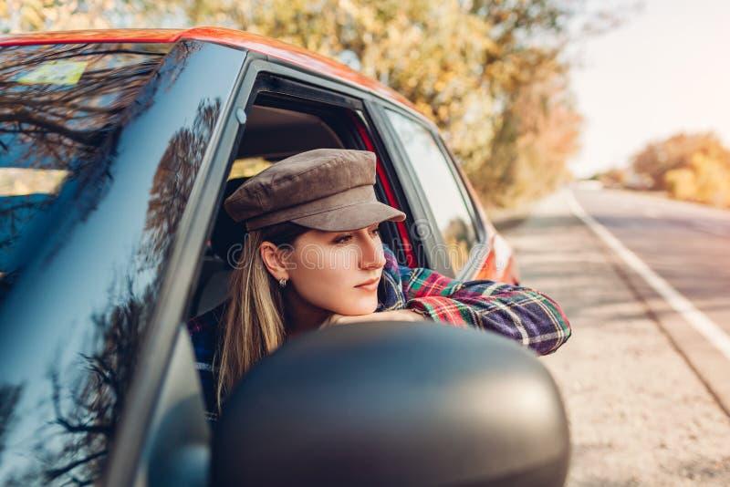 Женщина расслабляется в машине Водитель смотрит в окно autimobile на осенней дороге стоковое изображение rf