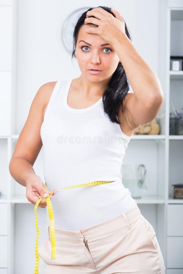 Женщина расстроена с измерением стоковое изображение rf