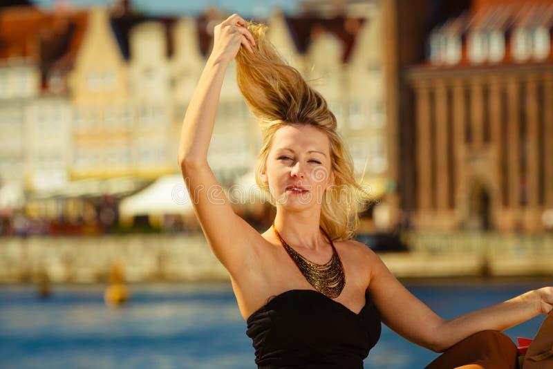 Женщина расчесывая ее волосы с пальцами, блестящее обмундирование стоковое изображение