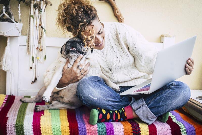 Женщина реальных лучших другов жизнерадостная работая на ноутбуке на террасе дома пока обнимите ее самую лучшую любовь и мопса со стоковые фото