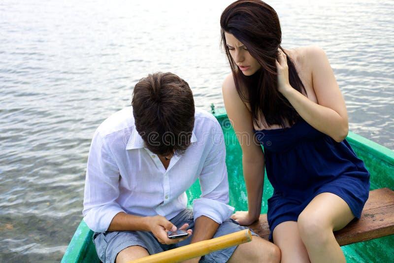 Женщина ревнивая о супруге на отправке СМС телефона стоковая фотография