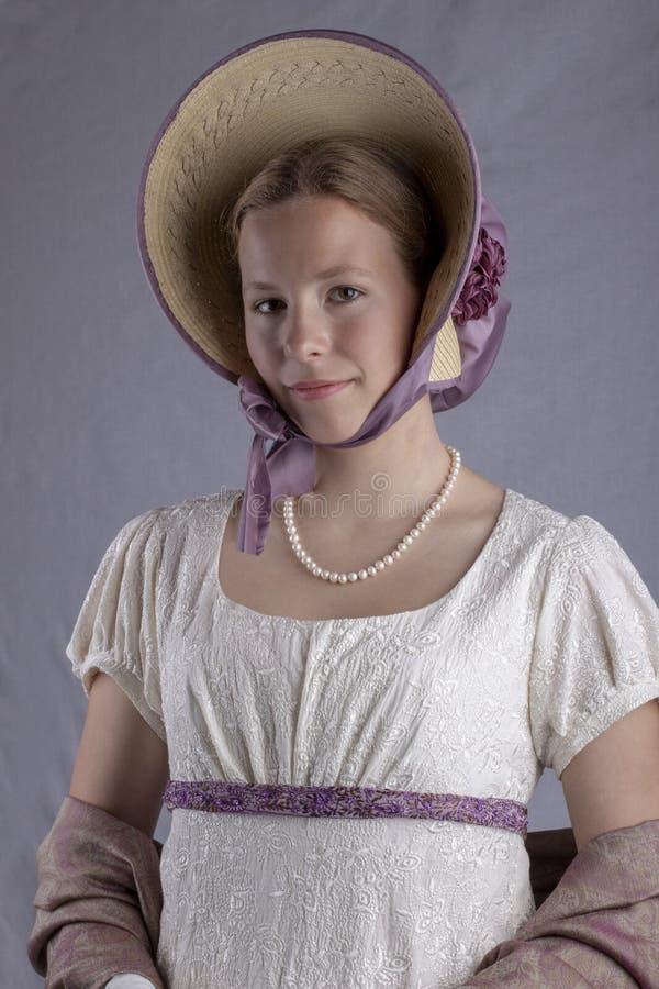 Женщина регентства в платье сливк и bonnet на фоне студии стоковые изображения rf