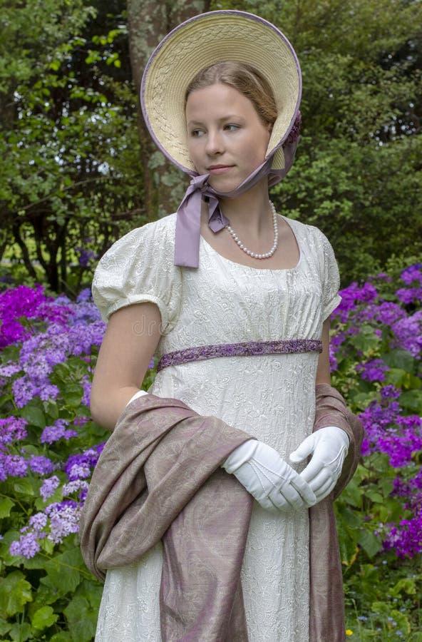 Женщина регентства в платье сливк, шали Пейсли и bonnet стоковые изображения