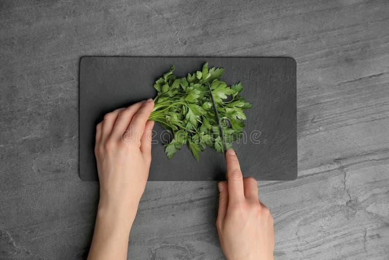 Женщина режа свежую зеленую петрушку на доске шифера на серой таблице стоковые изображения