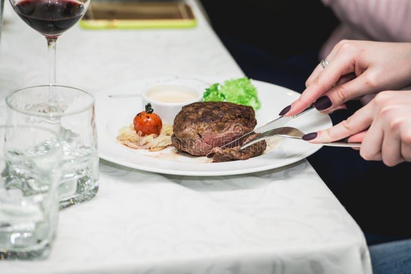 Женщина режет часть свежего зажаренного стейка ростбифа bbq соус супа малое стекло кувшина служил на таблице в ресторане стоковая фотография rf