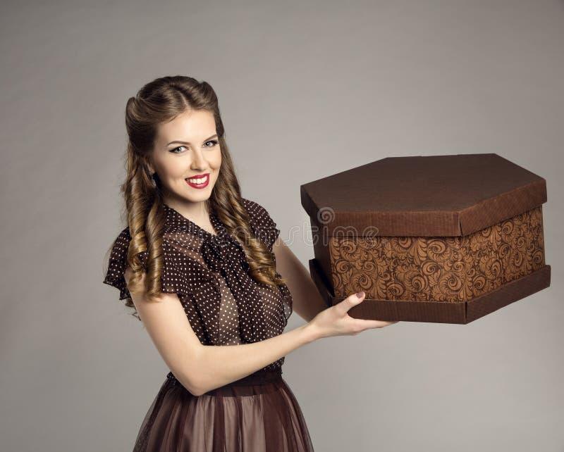 Женщина рекламирует подарочную коробку торта присутствующую, ретро девушку еда поставляет стоковая фотография rf