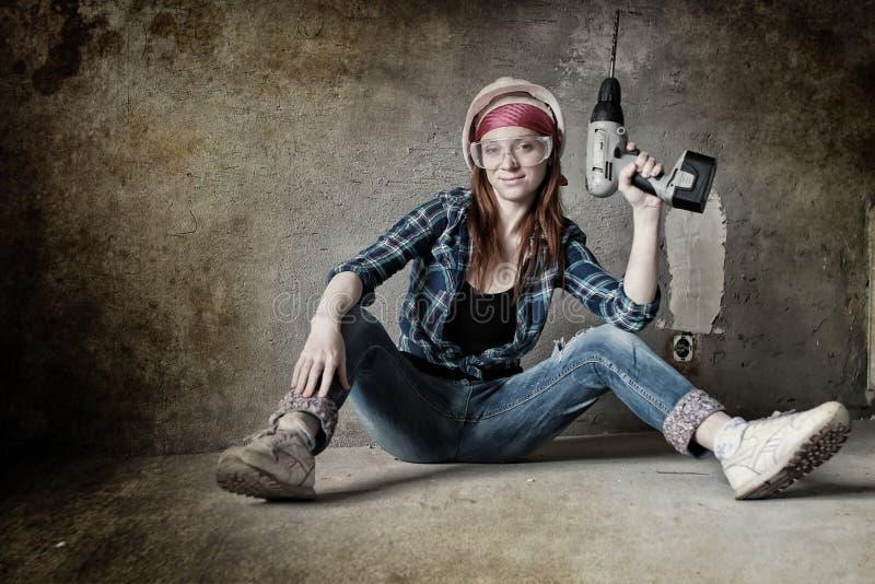 Женщина ремонтов здания стены с оборудованием стоковые фото