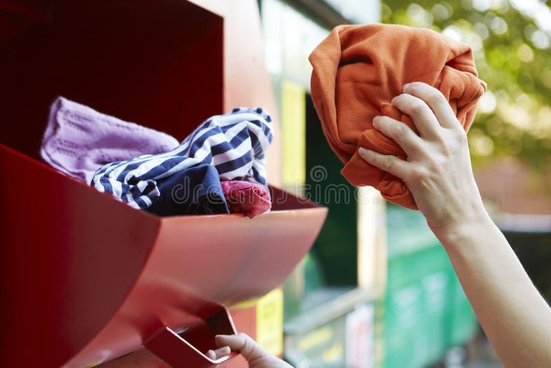 Женщина рециркулируя одежды на банке одежды стоковые фото