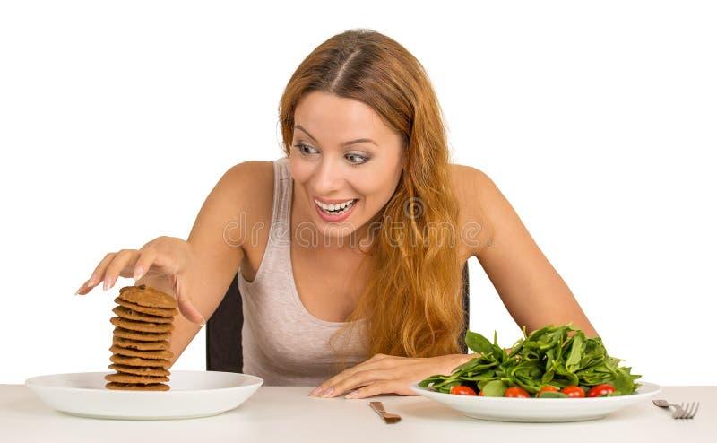 Женщина решая ли съесть здоровую еду или сладостные печенья стоковые фотографии rf