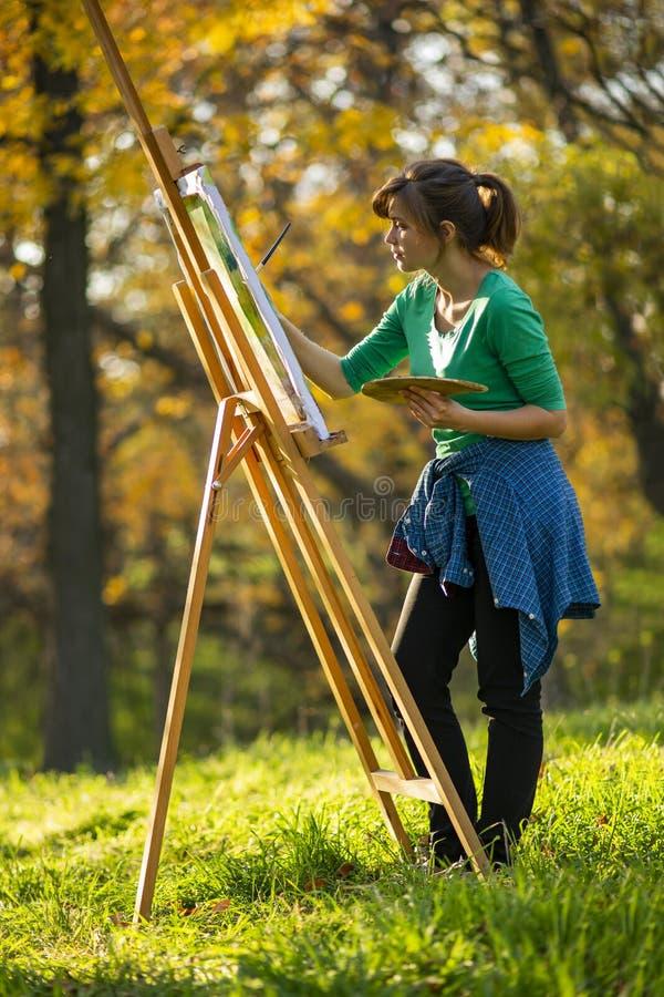 Женщина рисуя изображение на холсте на мольберте в природе, девушке с щеткой и палитре красок в красивом ландшафте, a стоковые фото