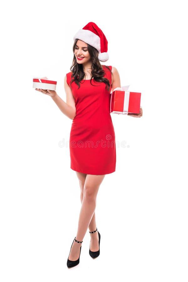 Женщина рождества держа подарки баланса нося шляпу Санты Стоять в полном теле изолированном на белой предпосылке Усмехаясь portra стоковое фото