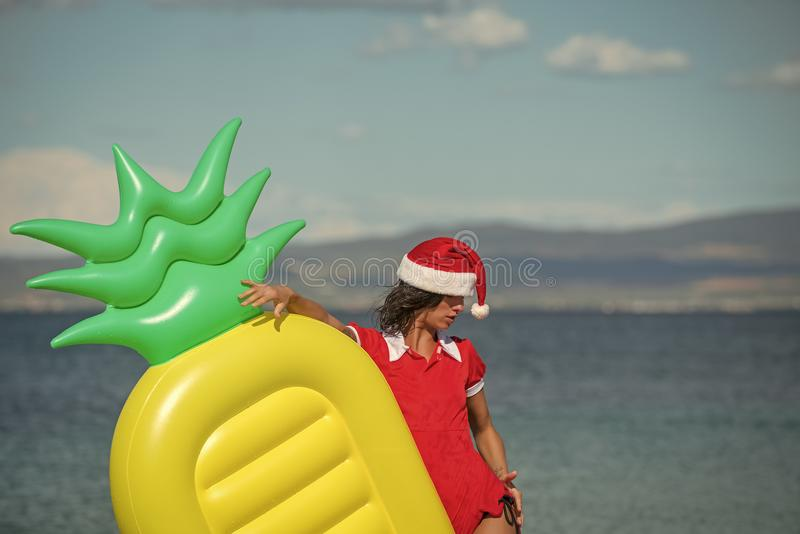 Женщина рождества с тюфяком ананаса в воде стоковые фото