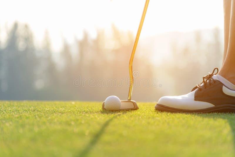 Женщина руки азиатская кладя шар для игры в гольф на тройник с клубом в поле для гольфа на выравнивать время для здорового спорта стоковое изображение