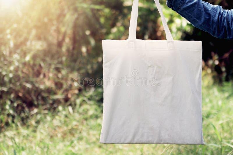 женщина руки держа сумку Tote хлопка на предпосылке зеленой травы стоковые фото