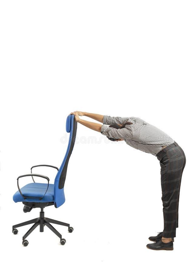 Женщина рядом с ее стулом офиса делая тренировки, изолированные на белизне стоковые фотографии rf