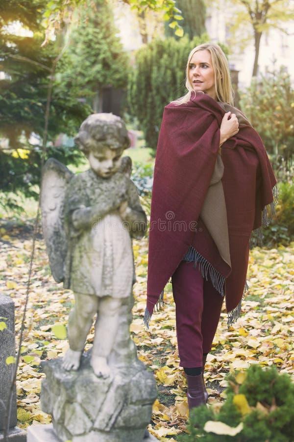 Женщина рядом с могилой с ангелом стоковое изображение rf