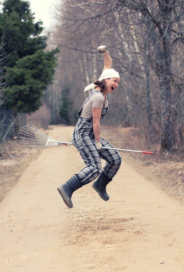 Женщина садовника или фермера летает на грабл, как ведьма на broo стоковые фотографии rf