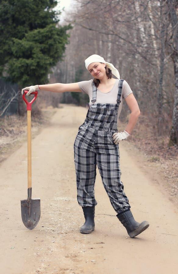 Женщина садовника или фермера стоя на сельской дороге с лопатой Автошина стоковое изображение