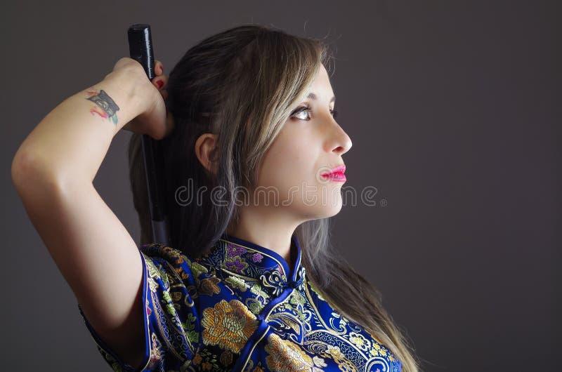 Женщина самураев одела в традиционном красочном платье картины цветка азиатском silk, держа руку над шпагой плеча хватая стоковые фото