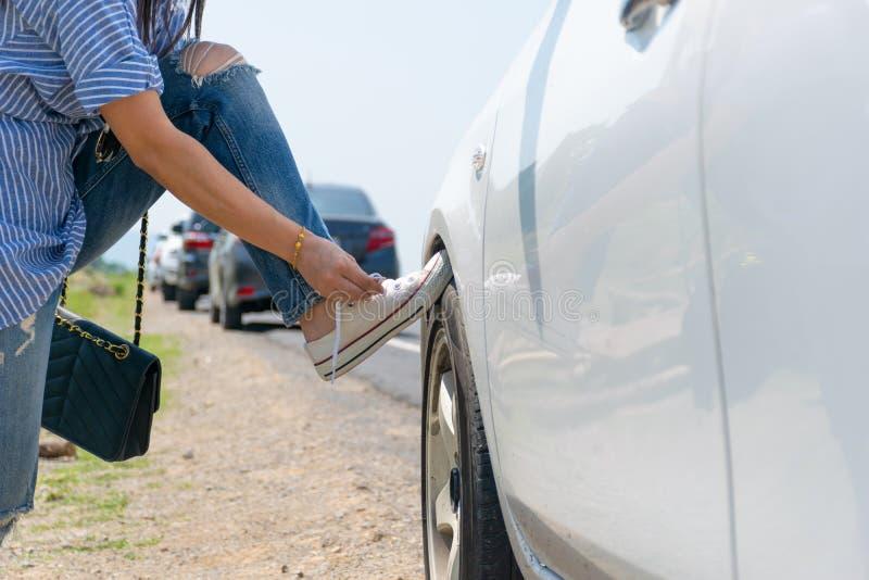 Женщина связала строку ботинка на колесе автомобиля стоковые фотографии rf