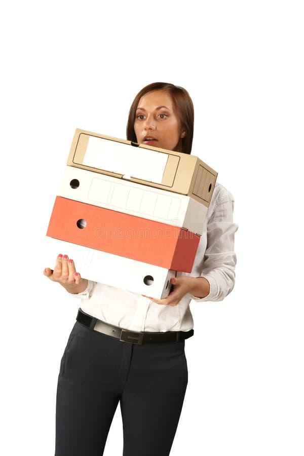 Женщина секретарши с большим стогом папок изолированных на белой предпосылке стоковое изображение rf