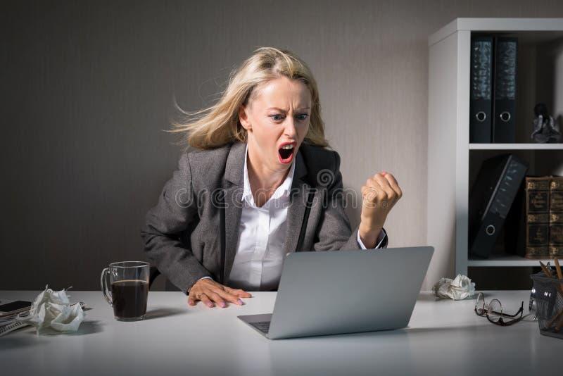Женщина сердитая на ее ноутбуке на работе стоковые изображения rf