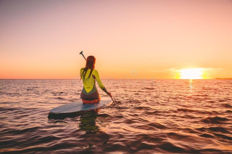 Женщина серфера дальше стоит вверх доска затвора на тихом море с теплыми цветами захода солнца Ослаблять на океане стоковое фото