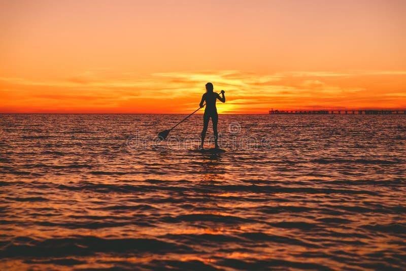 Женщина серфера стоит вверх восхождение на борт затвора на сумраке на плоском теплом тихом море с красивыми цветами захода солнца стоковая фотография rf