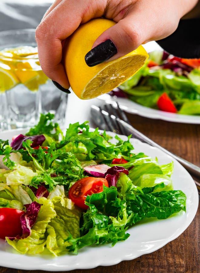 Женщина сжимает лимонный сок на различных свежих листьях салата, а помидор в белой тарелке стоковые фото