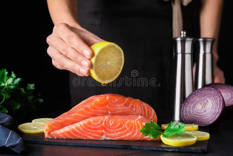 Женщина сжимает лимон на свежем сыром лосось за столом Рыбная деликатность стоковое фото rf