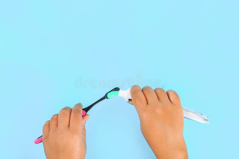 Женщина сжимая зубную пасту на щетке против голубой предпосылки цвета скопируйте космос Взгляд сверху стоковые изображения rf