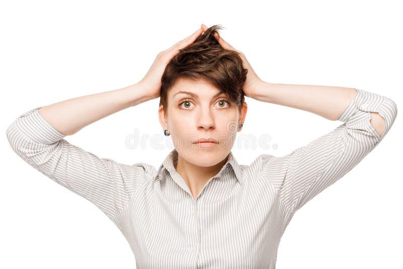 женщина сжимала ее голову в панике на белой предпосылке стоковые изображения
