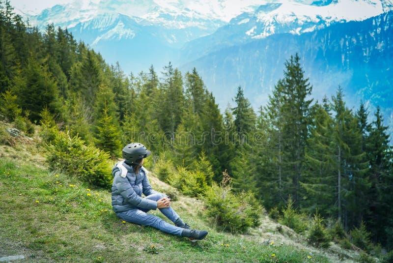 Женщина сидит вниз на траве смотря к горе и озеру стоковые фото