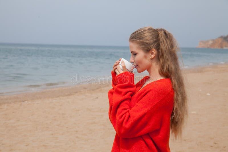 Женщина сидит на дезертированном песчаном пляже смотря на море стоковые изображения rf