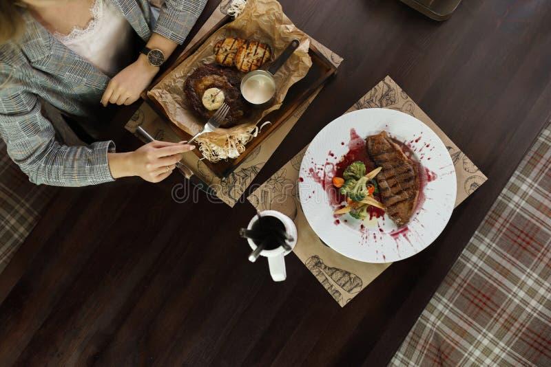 Женщина сидит на деревянном столе и ест сочный стейк говядины с зажаренными кусками баклажана с соусом сметаны вкусный обед стоковые изображения