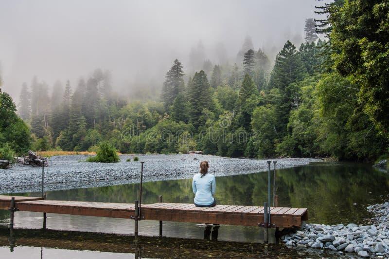 Женщина сидит на простом деревянном Footbridge стоковые фотографии rf
