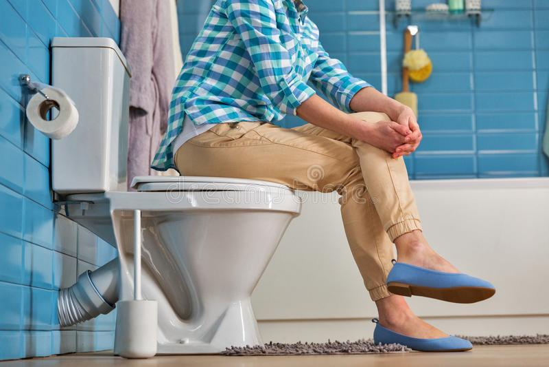 Женщина сидит на шаре туалета в ванной комнате, нижнем взгляде стоковое фото rf