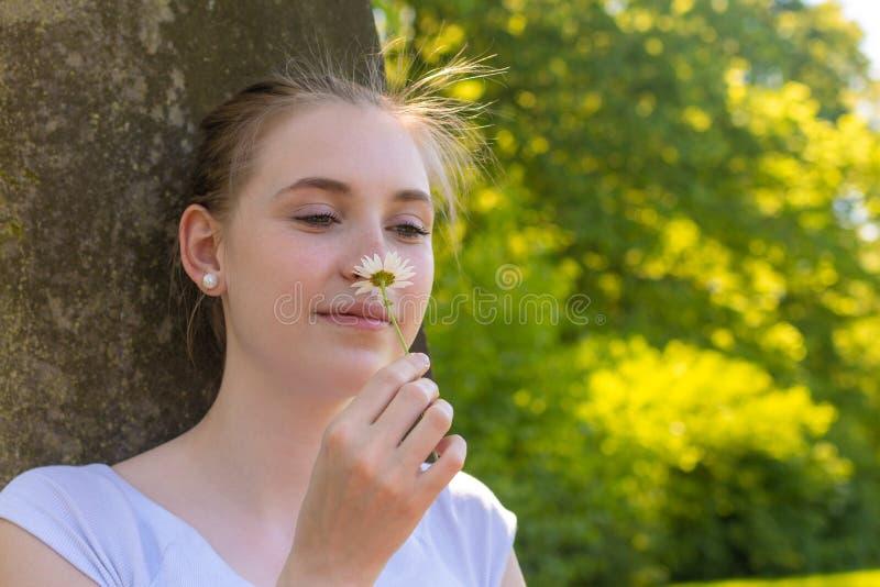Женщина сидит под деревом и пахнет на цветке стоковые фото