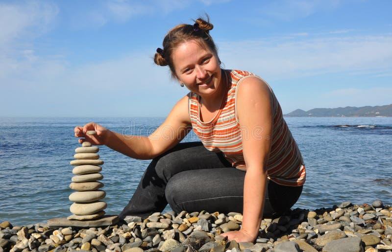 Женщина, сидящая на пляже возле кэрна стоковые фотографии rf
