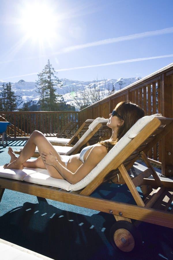 Женщина сидя в бикини в снежных горах стоковые фотографии rf
