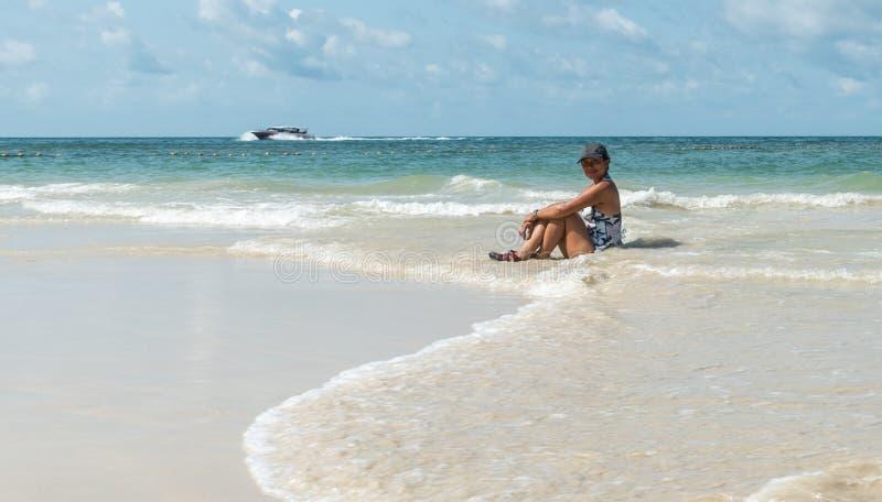 Женщина сидя в воде на пляже стоковое фото