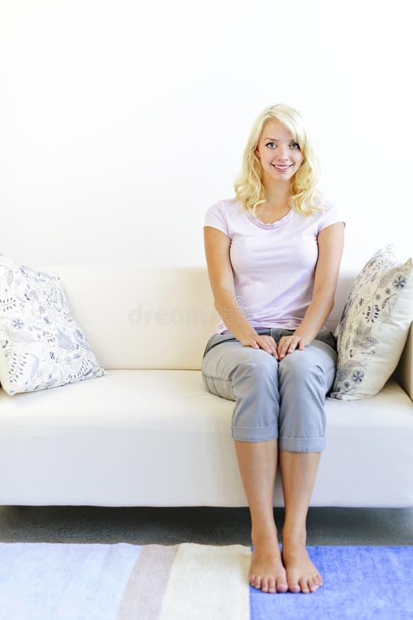 Женщина сидя в живущей комнате стоковые изображения rf